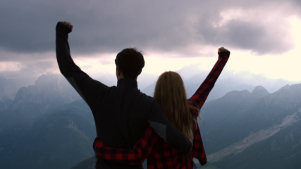 overhead-shot-happy-hiking-couple-raise-arms-in-celebration-of-reaching-the-mountain-top_raetqhgu__F0005